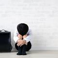 居間に一人で落ち込んだ様子で座っている子供と黒いランドセル