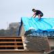 台風15号の被害を受けた住宅では、屋根をブルーシートで覆う作業が続けられていた=2019年9月22日午前、千葉県南房総市、長島一浩撮影