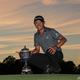 世界ゴルフ選手権(WGC)シーズン初戦、ワークデー選手権最終日。トロフィーを横に優勝を喜ぶコリン・モリカワ(2021年2月28日撮影)。(c)Sam Greenwood/Getty Images/ AFP