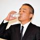 会見の途中で水を飲む岡本社長=東京都新宿区