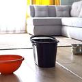 天井からの水漏れをバケツや皿で受け止めているリビング