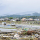 妻を助けて亡くなった井上三郎さんらが住んでいた熊本県人吉市下薩摩瀬町で、断続的に雨が降る中、行方不明者の捜索をする警察官ら=7日午前、熊本県人吉市