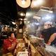 時短営業を決めた歌舞伎町の居酒屋で、感染予防のビニール越しに会話する男性客(左)と店員の男性=東京都新宿区で2020年8月3日午後5時7分、吉田航太撮影