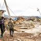 千曲川の堤防が決壊した場所のすぐそばでは家が数軒流され、電柱が傾いていた。奥に自宅があるという住民らがぼうぜんと見つめていた=2019年10月14日午前10時53分、長野市穂保、田中奏子撮影