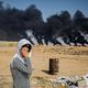 シリア北東部の対トルコ国境沿いにあるクルド人の町ラスアルアイン近郊で、トルコ軍戦闘機の視界を遮るためにたかれた煙を背に、顔を覆う女性(2019年10月16日撮影)。(c)Delil SOULEIMAN / AFP
