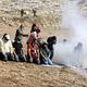 パレスチナ自治区ヨルダン川西岸のナブルスの東のベイトダジャン村付近で、ユダヤ人入植地の拡大に反対するデモ隊を排除するためイスラエルの治安部隊が発射した催涙ガスが漂う中で礼拝するパレスチナ人のデモ参加者ら(2020年10月9日撮影、資料写真)。(c)JAAFAR ASHTIYEH / AFP