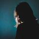 暗闇の中に立つうつ病の女性のシルエット