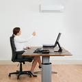 エアコンの温度調整をする女性