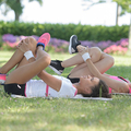 Women exercising outdoors, hugging knees to chest