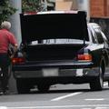 お抱えの運転手が車椅子を自宅に運び入れる