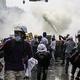 2日、ミャンマーの最大都市ヤンゴンで、催涙ガスを浴びるデモ隊(AFP時事)