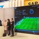 SAPのサッカー分析システム「マッチ・インサイト」の説明を受けるドイツのメルケル首相と、イギリスのキャメロン首相。サッカー好きで知られるメルケル首相は、ドイツ代表の初戦に続き決勝戦もブラジルで直接観戦したという。説明している長身の男性は、元ドイツ代表フォワードのオリバー・ビアホフ氏。現在ドイツ代表チームのマネージャーとしてデータ分析の陣頭指揮を執る