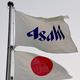 アサヒグループホールディングスのロゴの入った旗と日の丸(2016年4月19日撮影)。(c)TOSHIFUMI KITAMURA / AFP