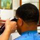 縮れ毛で硬くて多い、複雑な髪質のアフリカ系の人たちが店に殺到する。熟練の技術者たちは、生え際のラインを特殊なバリカンで決め、細かくぼかしながら仕上げていく=相模原市南区相武台1丁目