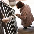 手すりにつかまりながら階段を下りる年配の女性