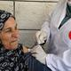 パレスチナ自治区ヨルダン川西岸の都市ヘブロン近郊のデュラで、高齢者にワクチンを接種するパレスチナ保健省職員(2021年6月9日撮影)。 (c)HAZEM BADER / AFP