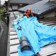 瓦の落下で穴があいた屋根をブルーシートで覆う大工の佐藤博繁さん=2019年6月19日午前11時18分、新潟県村上市府屋、恵原弘太郎撮影