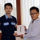 千葉市役所で熊谷俊人市長に見舞金を手渡す日本写真判定の渡辺俊太郎さん(右)