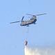 上空から散水して消火を試みる陸上自衛隊のヘリコプター(23日午後3時42分、足利市で)