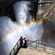 観光放水が始まった黒部ダム。水のアーチに虹が懸かった=2019年6月26日、富山県立山町、高津守撮影
