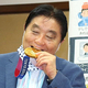 首に掛けてもらった金メダルにかみつく名古屋市の河村たかし市長=4日、同市役所