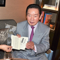 ファンのために、自伝本にサインをする生前の野粼幸助氏。