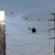 イスラエルにあるタワー式太陽熱発電所(ソーラータワー)のアシャリム発電所前で、ヘリコプターを使い電線を清掃する作業員。ネゲブ砂漠近くのキブツ(農業共同体)、アシャリムで(2021年6月8日撮影)。(c)Emmanuel DUNAND / AFP