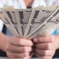 数枚の一万円札を持つ手元
