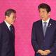 4日、バンコクで、安倍晋三首相(右)の前を通り過ぎる韓国の文在寅大統領(ロイター時事)