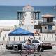 新型コロナウイルスの感染拡大防止のため閉鎖された米カリフォルニア州マンハッタンビーチで自転車に乗る人たち(2020年7月4日撮影)。(c)Robyn Beck / AFP