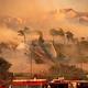 米カリフォルニア州ポーターランチで、風が吹く中で森林火災の消火活動に当たる消防隊員ら(2019年10月11日撮影)。(c)Josh Edelson / AFP