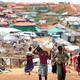食料や住宅用資材を運ぶ難民たちが行き交う=2018年8月5日、バングラデシュ南東部コックスバザール、杉本康弘撮影