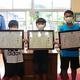 表彰された首藤響祐さん(左から2番目)ら3人=2020年6月29日午後3時8分、北九州市小倉北区の日明小学校、板倉大地撮影