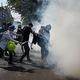 28日、ミャンマーの最大都市ヤンゴンで、警察が放った催涙ガスを消そうと試みる抗議デモ参加者(AFP時事)