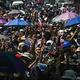 ミャンマー・ヤンゴンで、軍のクーデターに抗議するデモで死亡した人の葬儀が行われ、3本指を掲げて追悼する人々(2021年3月2日撮影)。(c)STR / AFP
