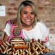 米ニューヨークで4日、自らが食べた分と同じ48.5個のホットドッグを前に、笑顔を見せる須藤美貴さん=AP