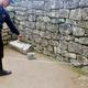 南米ペルーのマチュピチュ遺跡で、立ち入り禁止区域に侵入した外国人旅行者らによって剥がされた壁の石を指差す警察官(2020年1月12日撮影)。(c)AFP PHOTO / PERUVIAN NATIONAL POLICE