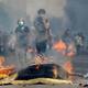 チリの首都サンティアゴで、兵士らと衝突するデモ参加者(2019年10月19日撮影)。(c)Pablo VERA / AFP