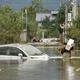 台風19号の洪水被害を受けた長野県で、自宅から家財品を運びながら冠水した道を歩く男性(2019年10月14日撮影)。(c)Kazuhiro NOGI / AFP