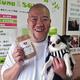 非常食「SONAE」を手に持ち、愛犬のサクラを抱く安井明彦さん