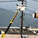 電線の点検、修理にあたる人たち。奥の家では一部の屋根瓦がはがれていた=2019年9月22日午前11時58分、宮崎県延岡市、菊地洋行撮影