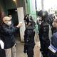 中核派の活動拠点「前進社」に家宅捜索に入る警視庁の捜査員ら。同派関係者(左)が検温を求める様子もみられた=16日、東京都江戸川区
