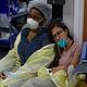 米テキサス州ヒューストンで、目を閉じて同僚の肩にもたれて休む医療従事者(右、2020年7月2日撮影)。(c)Mark Felix / AFP