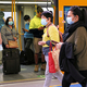 シドニーで23日、マスク姿で電車通勤する人たち=ロイター