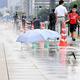 東京五輪に向けた暑さ対策で、歩道に設置したホースから散水し、路面温度などの上昇を抑える試みが行われた=東京都千代田区、2018年8月13日