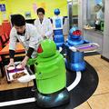 配膳専門ロボットのトレーの上に、料理を載せる人間の店員。ここ