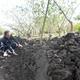 大量の土砂の横で「50センチほど堆積している」と説明する神田さん(長野県中野市で)