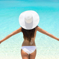Beach vacation bikini woman with open arms in freedom. Caref