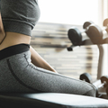 Young woman having back pain after workout at the gym.