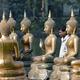 スリランカの仏像とその傍らに立つ男性(2017年2月10日撮影、本文とは関係ありません)。(c)LAKRUWAN WANNIARACHCHI / AFP